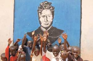 Children raise their hands in front of a mural of St. Bakhita at  a displacement camp  near Khartoum