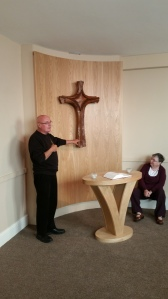 Fr. Column telling us about the cross in the Chapel - Sister Bridgetta looks on